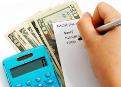 Calculator, Money, and a hand writing a budget