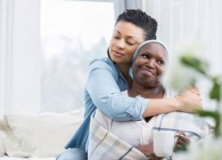 Mid adult African American woman embraces her ill senior mother.