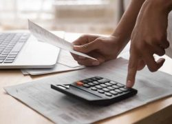 African woman holding in hand paper bills bank receipt using calculator on table calculate debt loan tax cost to pay manage finances concept doing accounting paperwork budget analysis, close up view