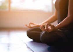 Women in meditation while practicing yoga in a training room. Happy, calm and relaxing.