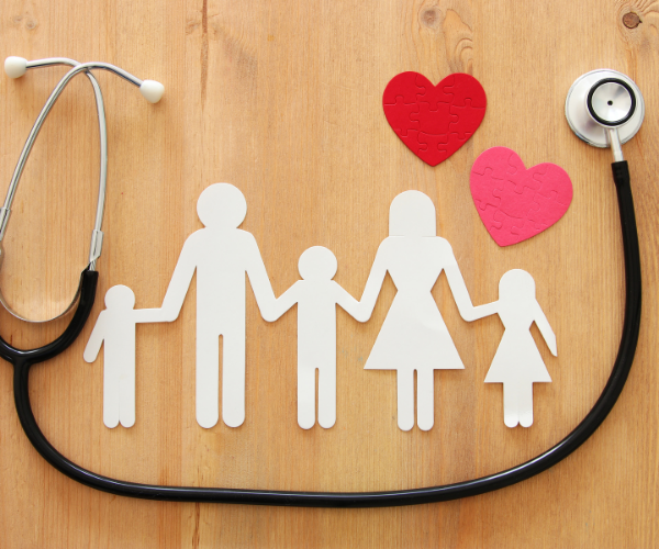 Free health insurance. A paper family holding hands.
